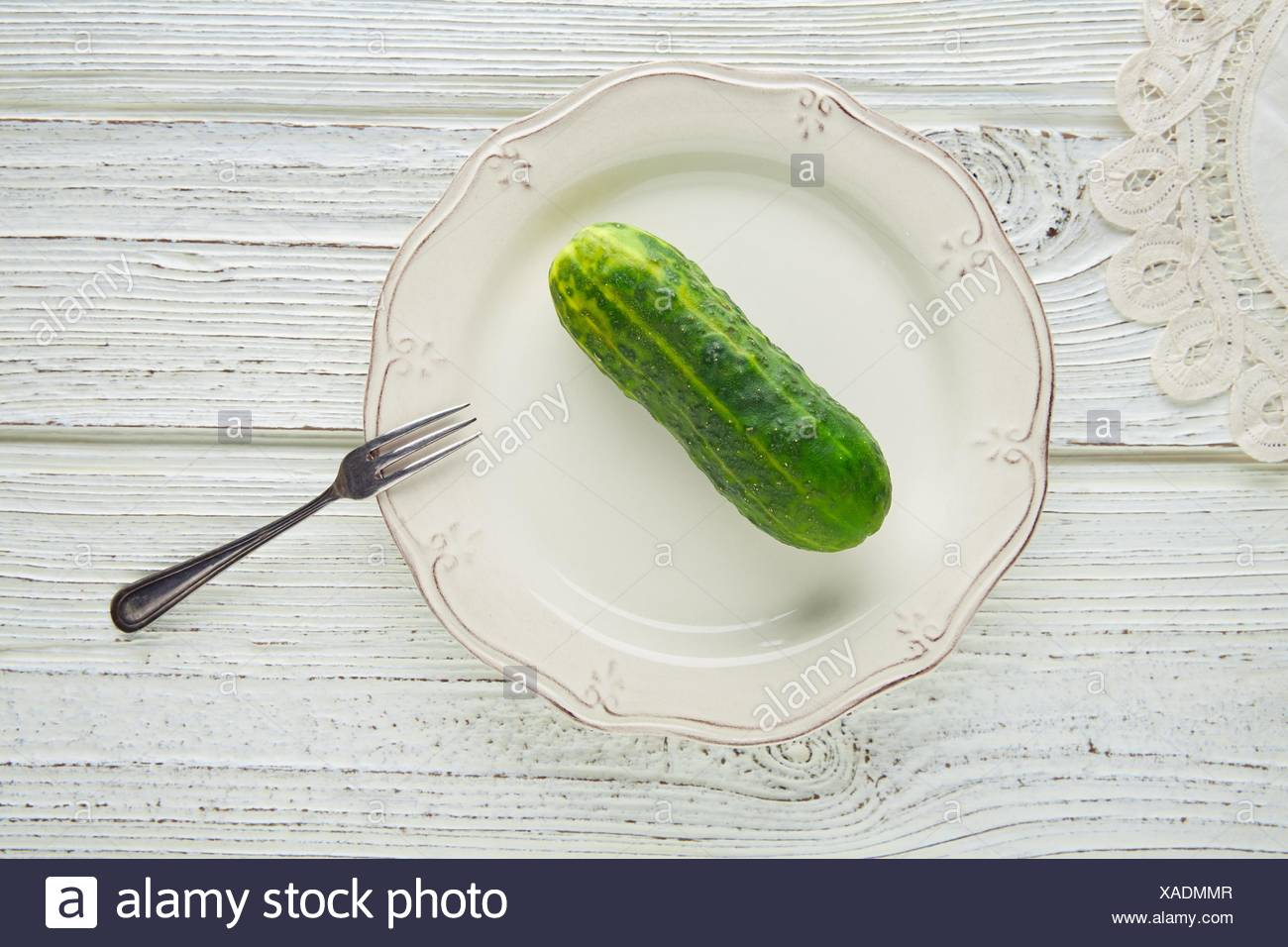 cucumber full in white plate minimalist concept of raw vegetarian food. - Stock Image