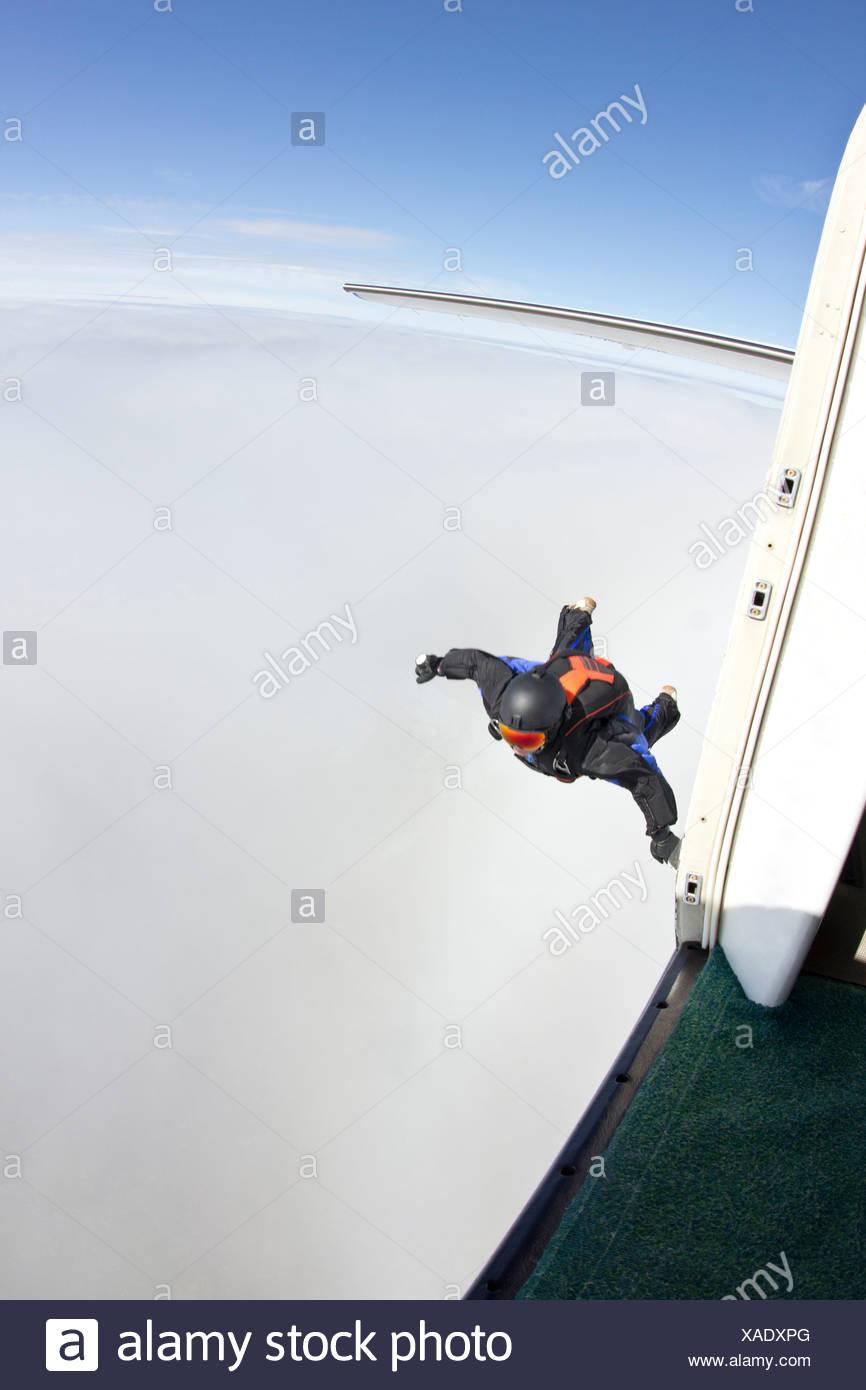 Mid adult man mid air preparing to fly in wingsuit - Stock Image