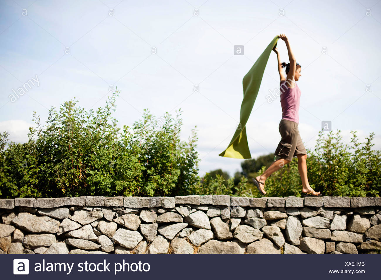 A woman pretends her green yoga mat is a cape while running on a stone ledge. - Stock Image