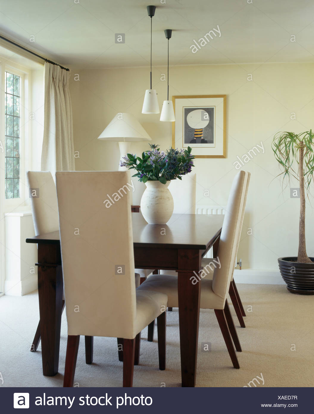 Cream Upholstered High Back Chairs And Dark Wood Table In Modern Dining Room With Carpet
