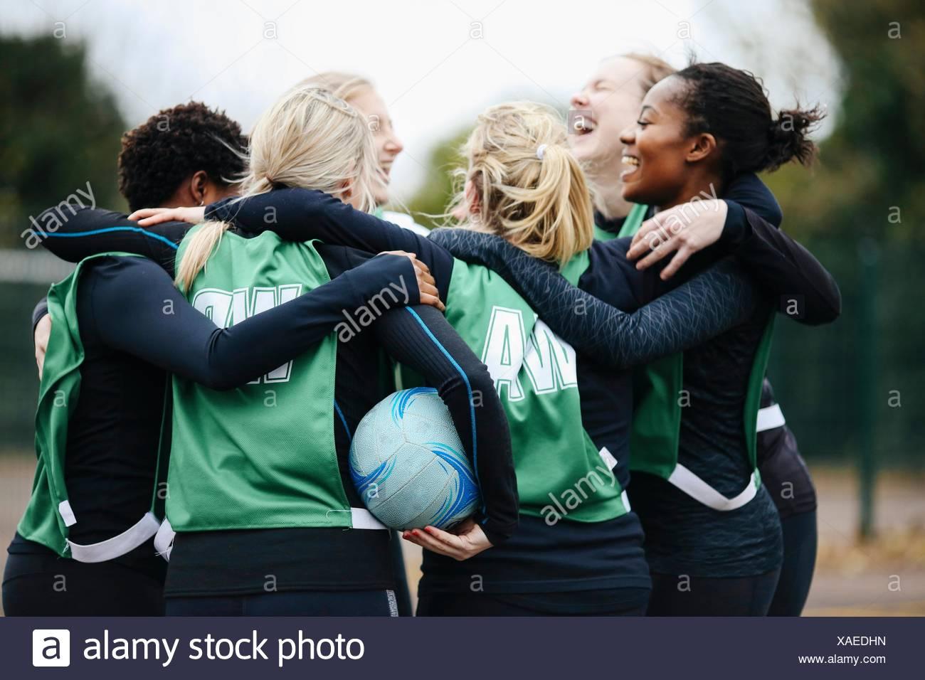 Female netball team celebrating in huddle on netball court - Stock Image