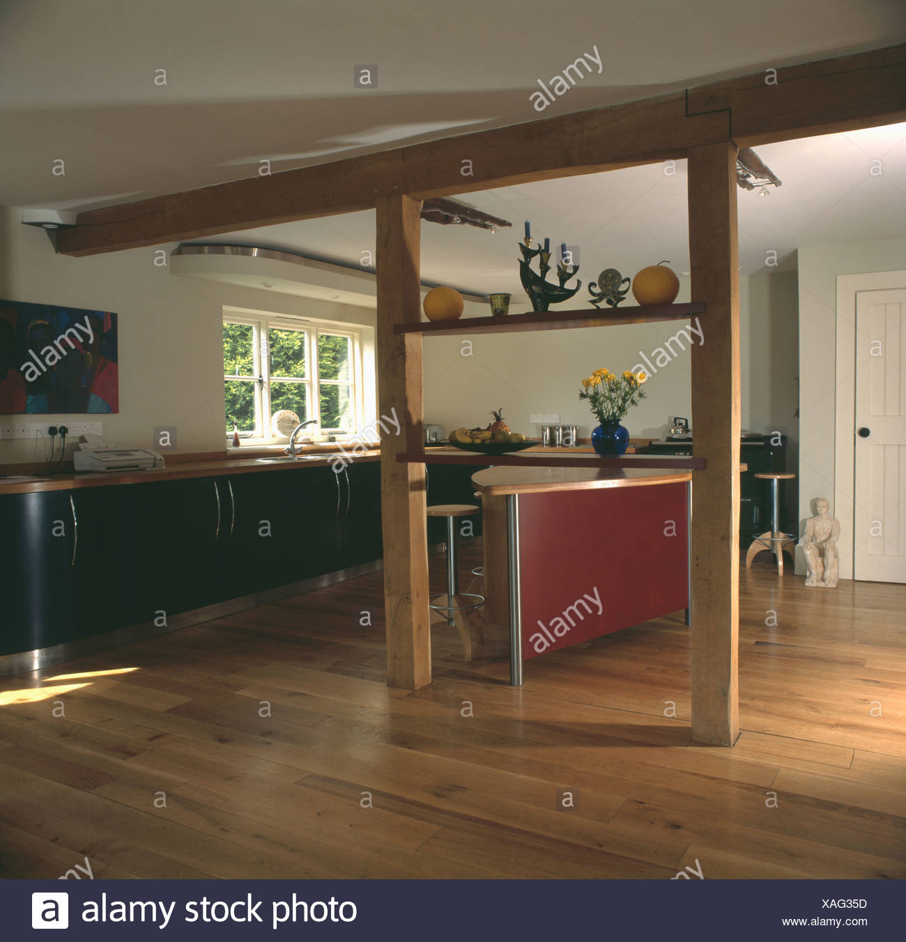 Wooden flooring in modern country kitchen with wall removed exposing upright and ceiling beams & Wooden flooring in modern country kitchen with wall removed exposing ...