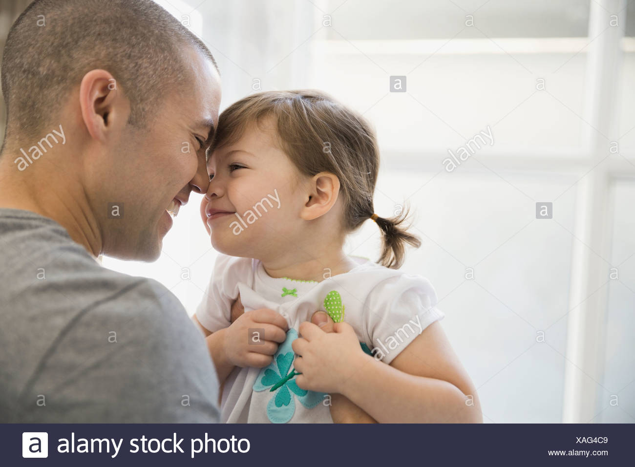 Father and daughter rubbing noses - Stock Image