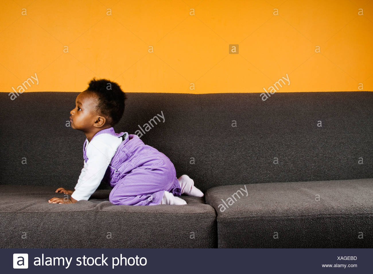 A baby girl on a sofa - Stock Image