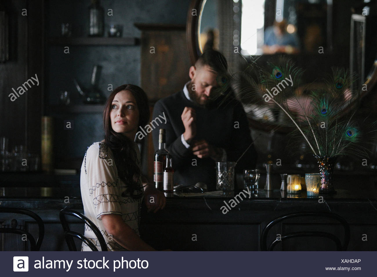 A woman and a bartender talking, and mixing drinks. - Stock Image