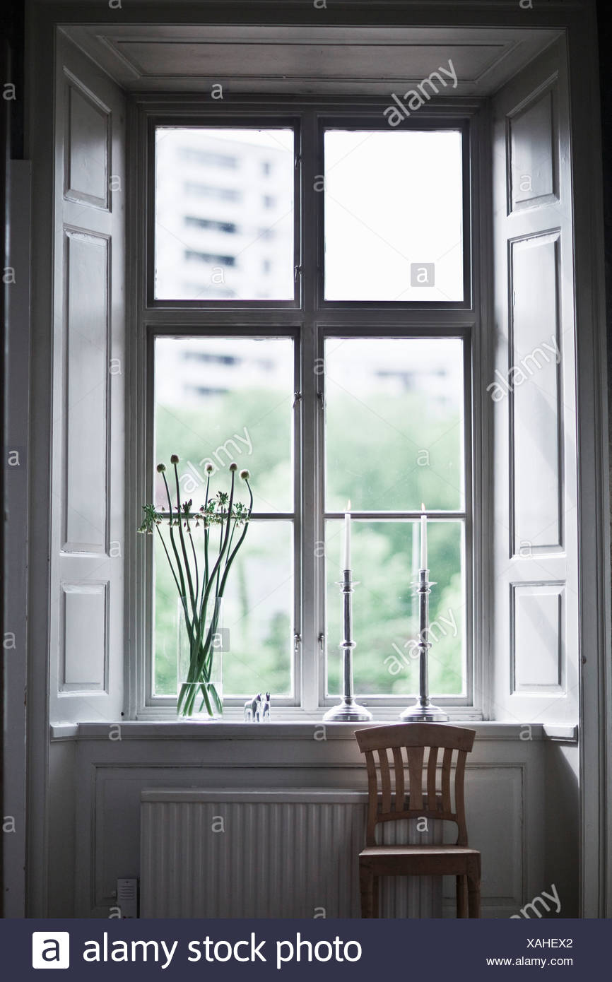 Chair standing by window - Stock Image