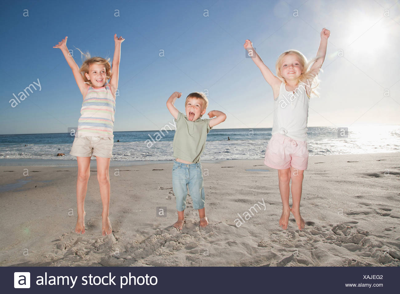Kids on beach with arms raised - Stock Image
