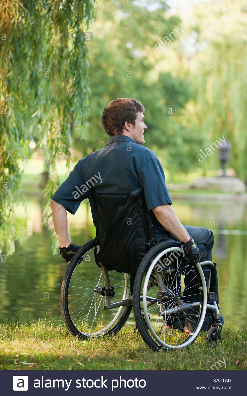 Man with spinal cord injury in a wheelchair in wheelchair enjoying at the pond side in public park - Stock Image