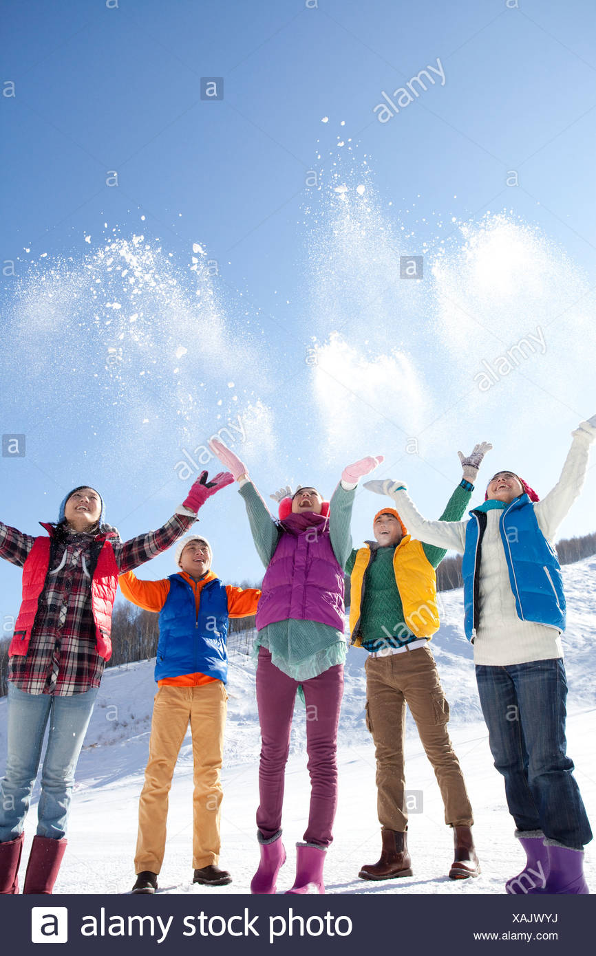 Young people having fun in snow - Stock Image