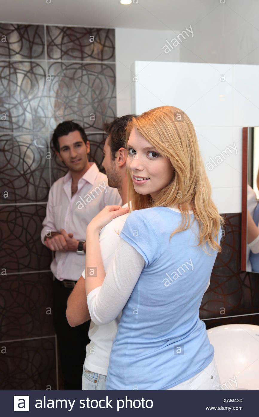 Woman hugging her boyfriend in a bathroom - Stock Image