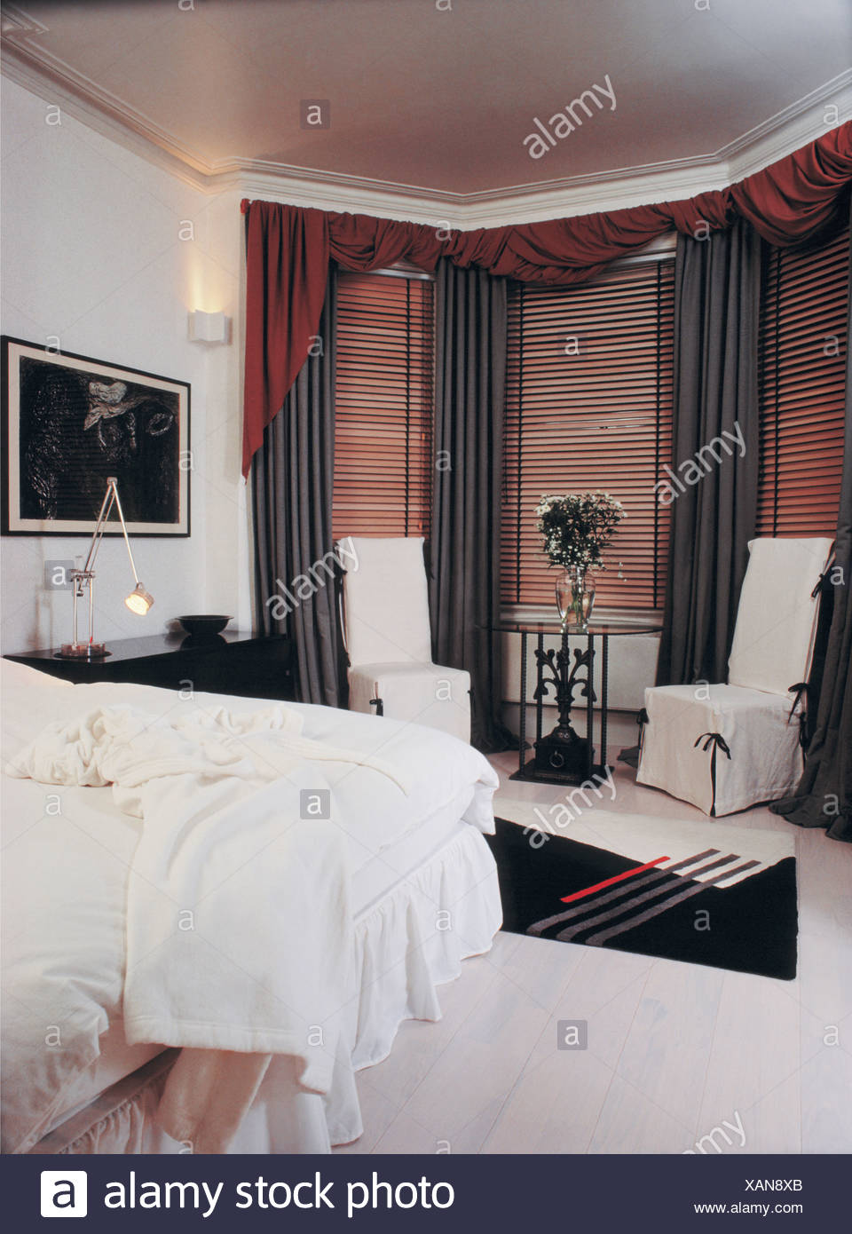 White Loosecovers On Chairs Beside Bay Window With Wooden Blinds And
