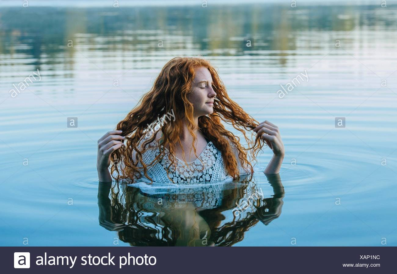 Head and shoulders of beautiful young woman with long red hair in lake - Stock Image