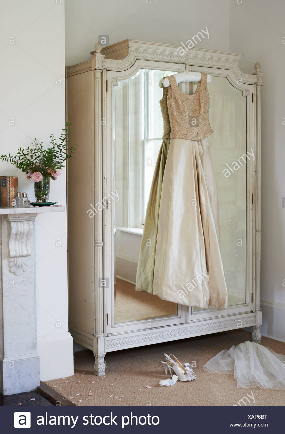 Wedding gown hanging from wardrobe - Stock Image