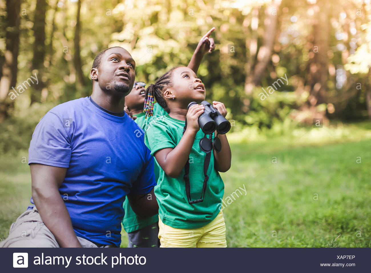 Young father with son and daughter bird watching in eco forest camp - Stock Image