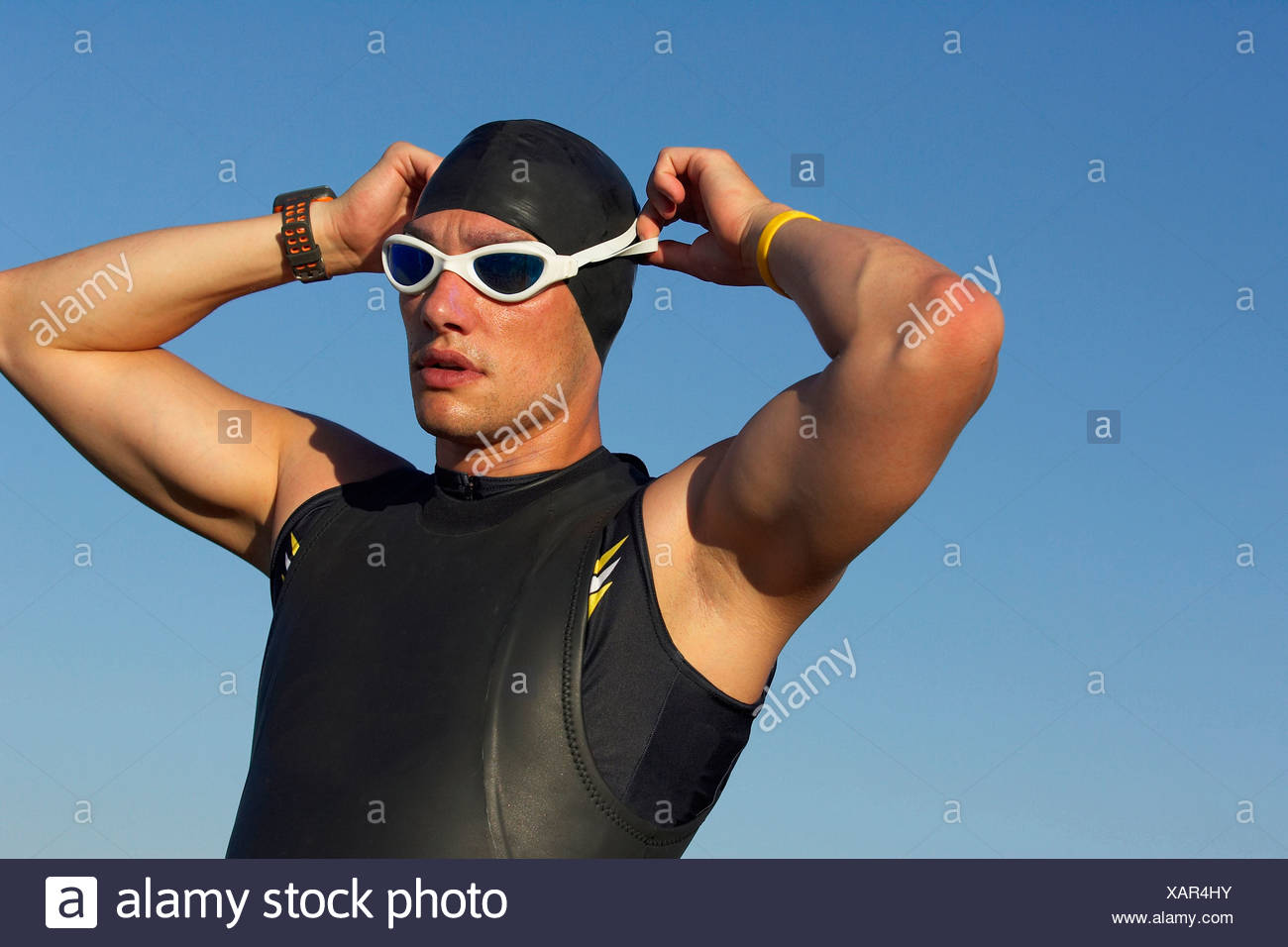 A male athelete preparing to swim while training for a triathlon. - Stock Image