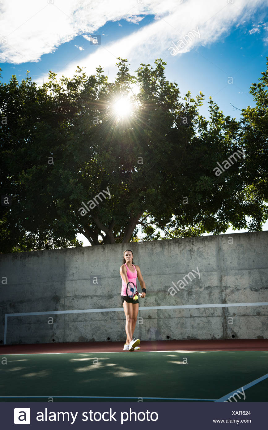 Female tennis player serving ball - Stock Image