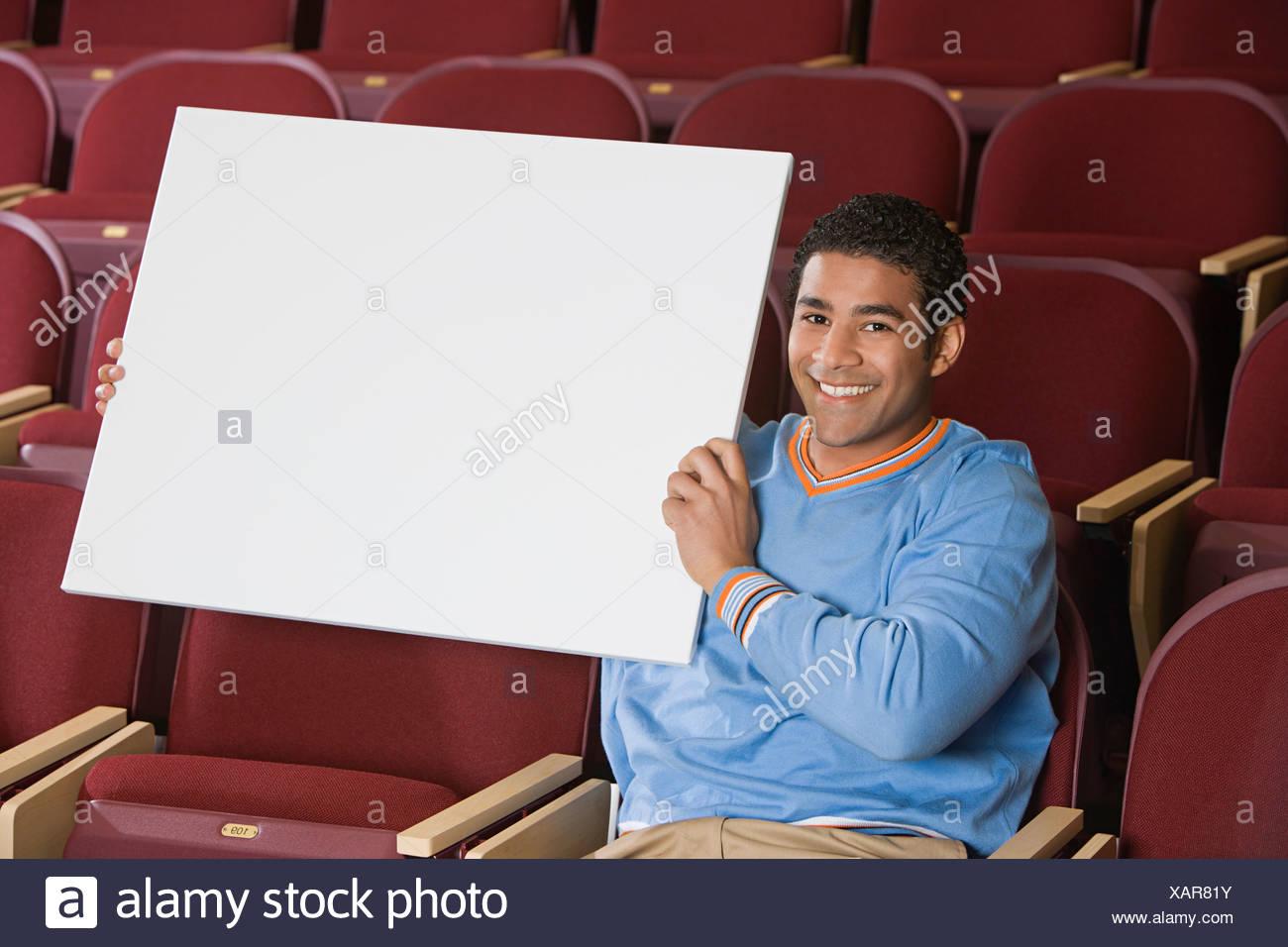 Man sitting in auditorium, holding empty placard - Stock Image