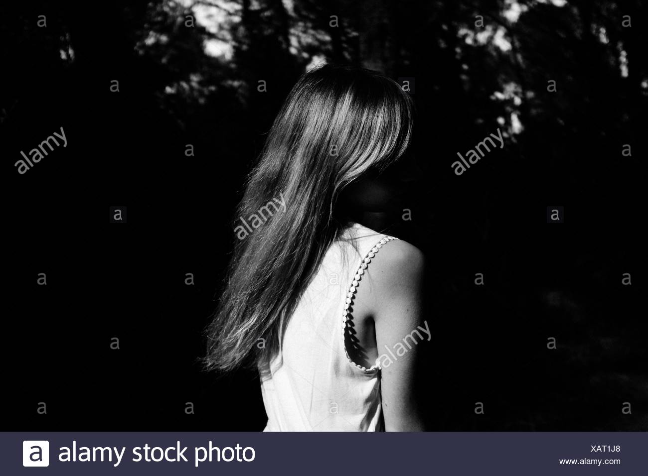 Rear View Of A Woman Against Dark Plants - Stock Image