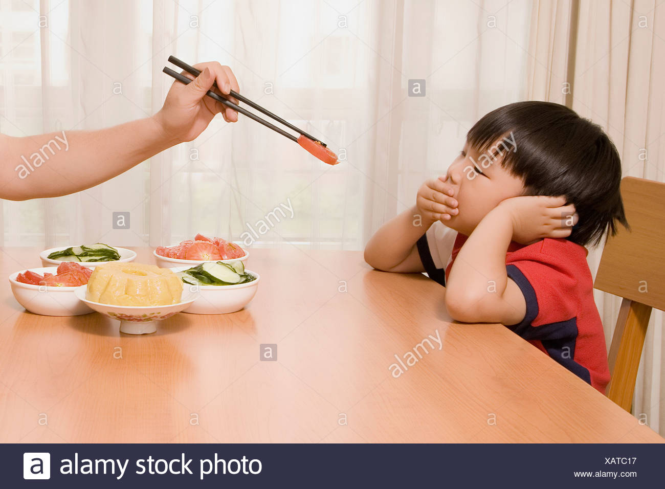 Person's hand holding chopsticks and feeding a boy - Stock Image