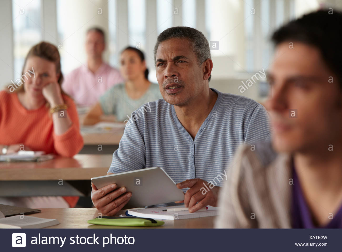 Man using digital tablet in class - Stock Image