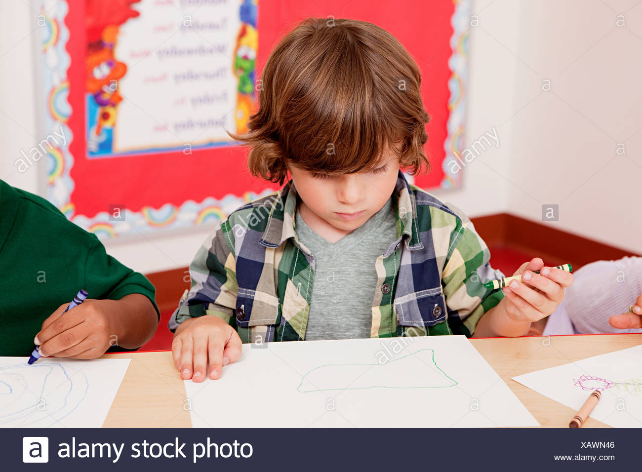 Boy drawing a picture in class - Stock Image