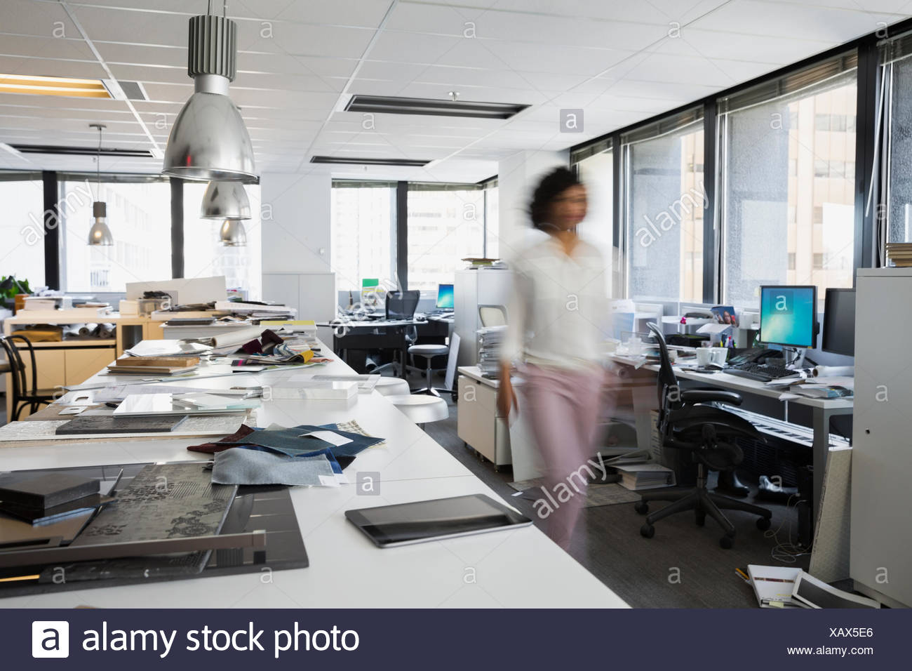 Blurred motion designer walking in office - Stock Image