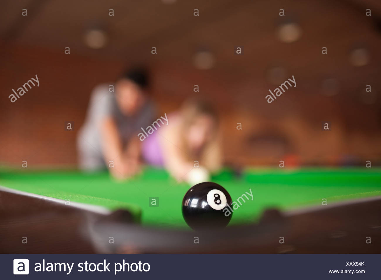 Man teaching pool to his fiance - Stock Image