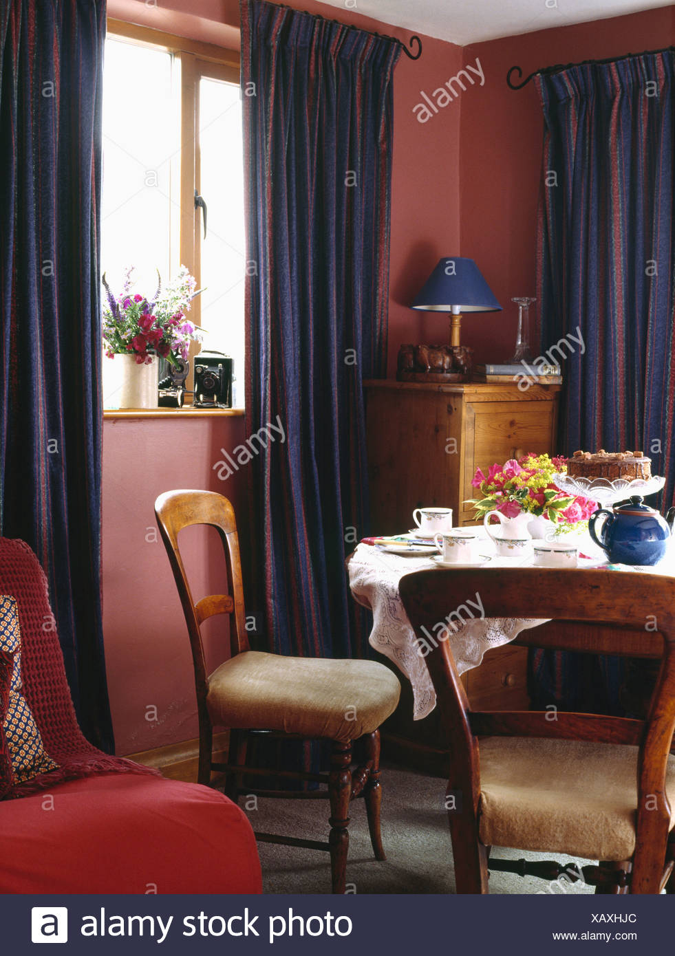 Dark Blue Curtains And Antique Chairs In Small Red Country Dining Room With  Teaset On The Table