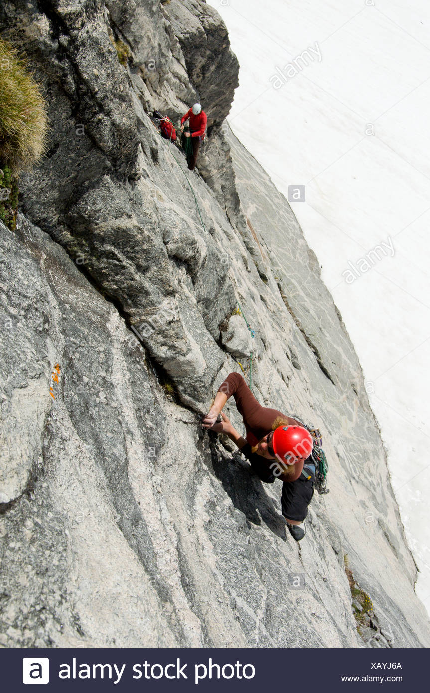 Two climbers tackle the impressive south face of Asgard Peak in the Valhalla Mountains, Selkirk Range, British Columbia, Canada - Stock Image