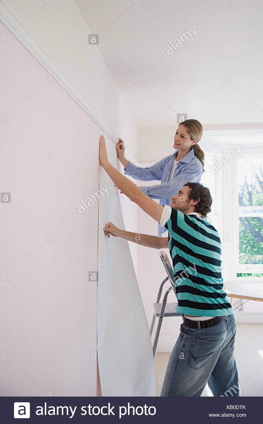 Couple putting up wallpaper - Stock Image