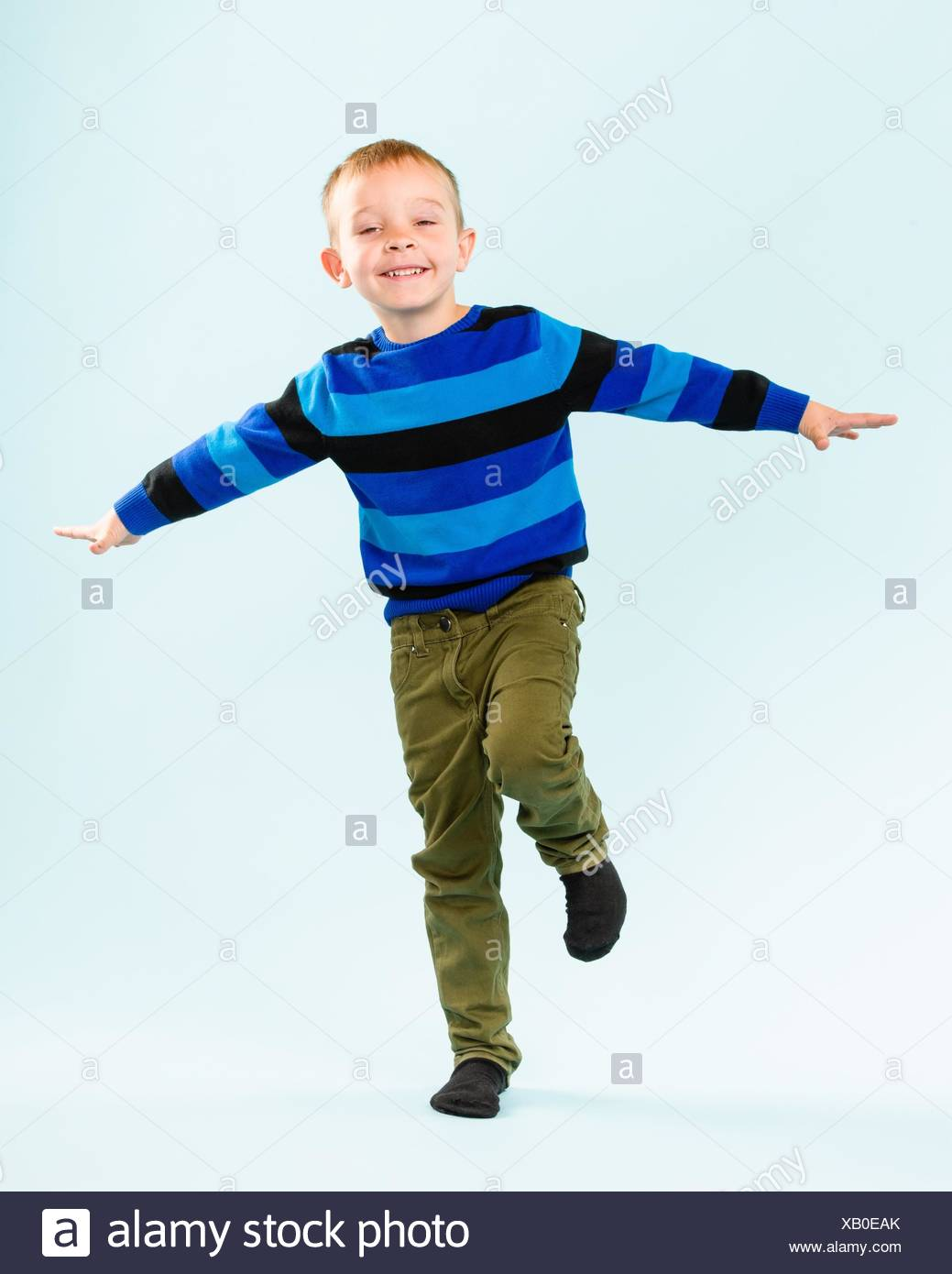 playful little boy on studio, light blue background stock photo