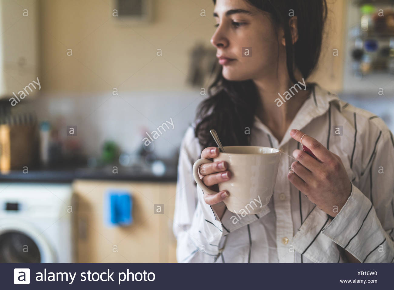 Young woman at home, wearing pyjamas, holding coffee cup - Stock Image