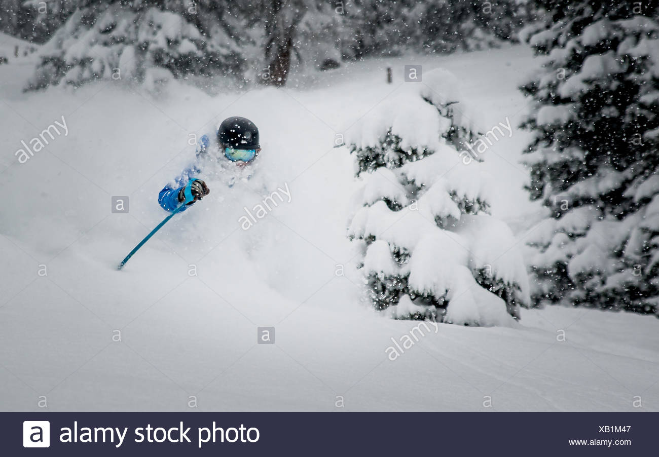 A male skier enjoying deep powder skiing in the Austrian Alps. - Stock Image