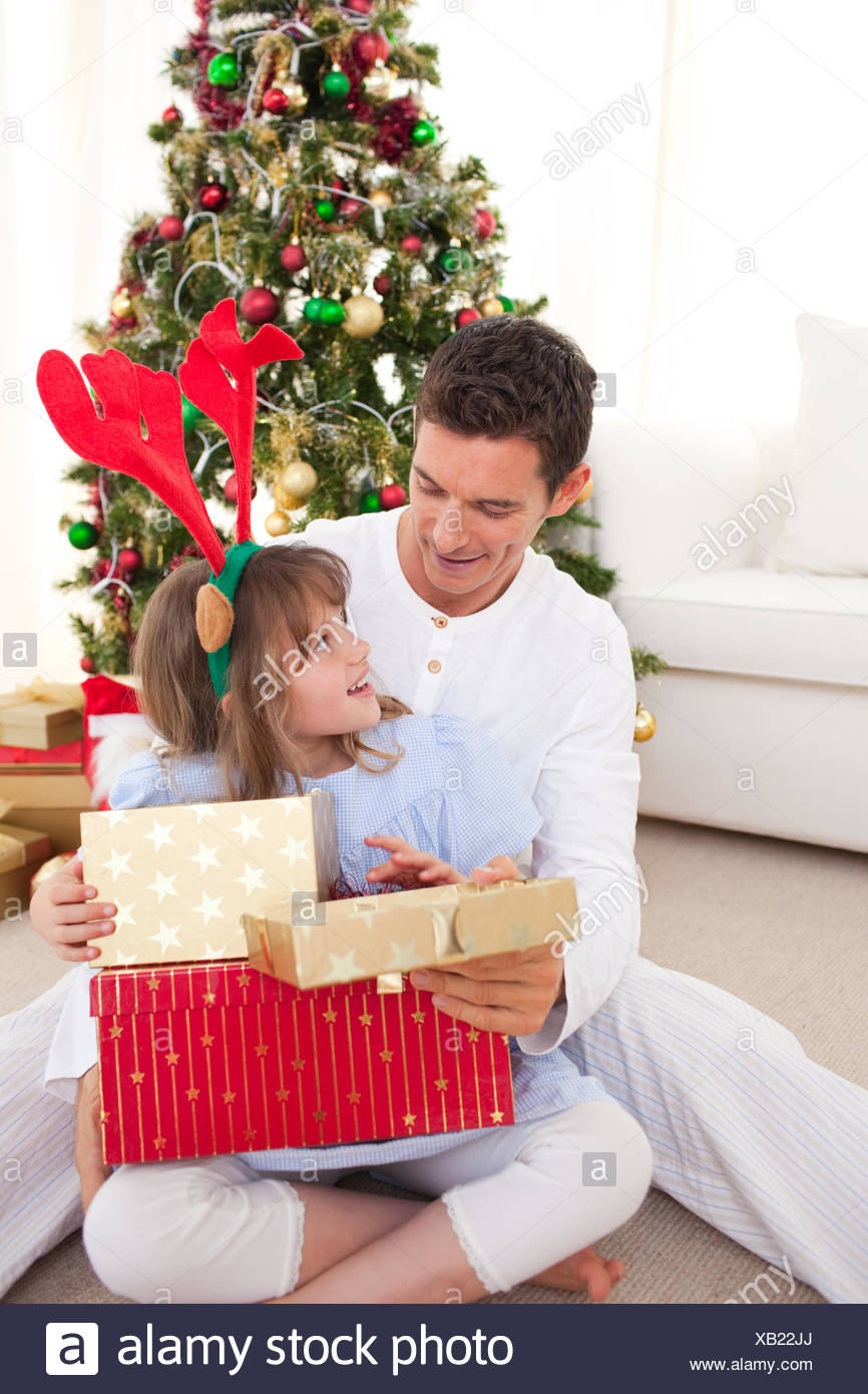 Smiling father and his daughter opening Christmas gifts Stock Photo ...