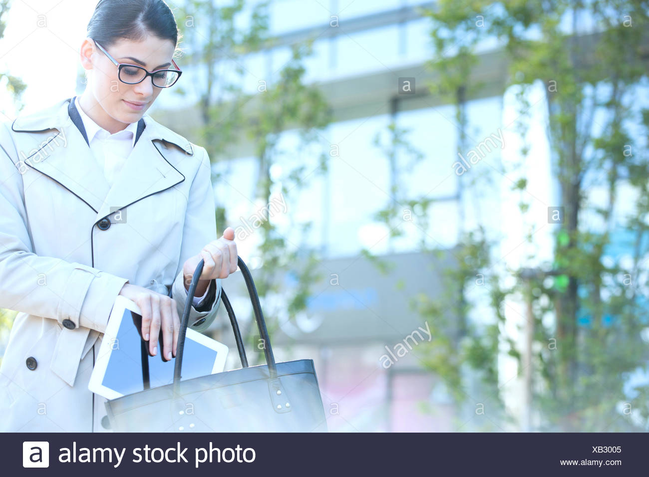 Businesswoman putting digital tablet in purse outdoors - Stock Image