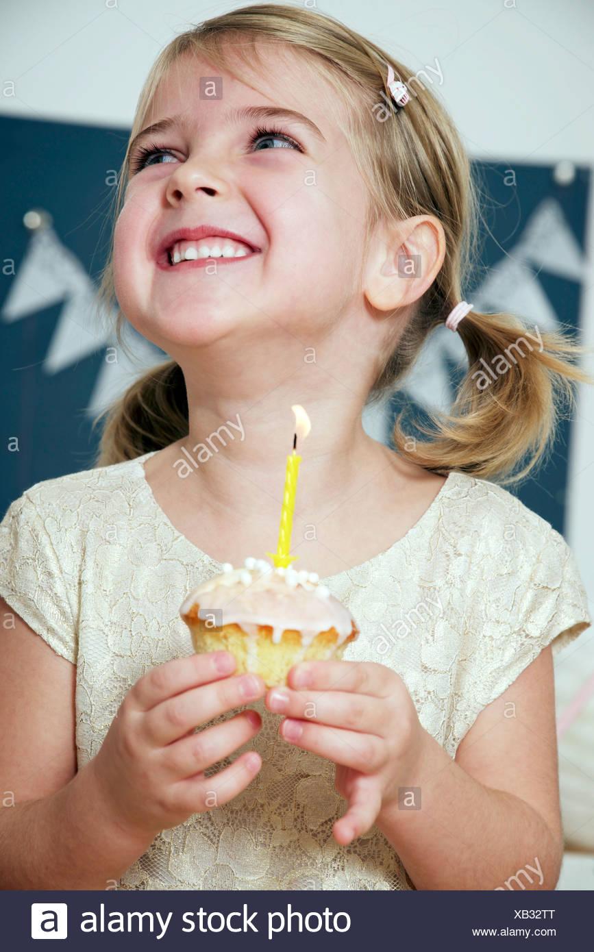 Girl on birthday party holding cupcake wit burning candle, Munich, Bavaria, Germany - Stock Image