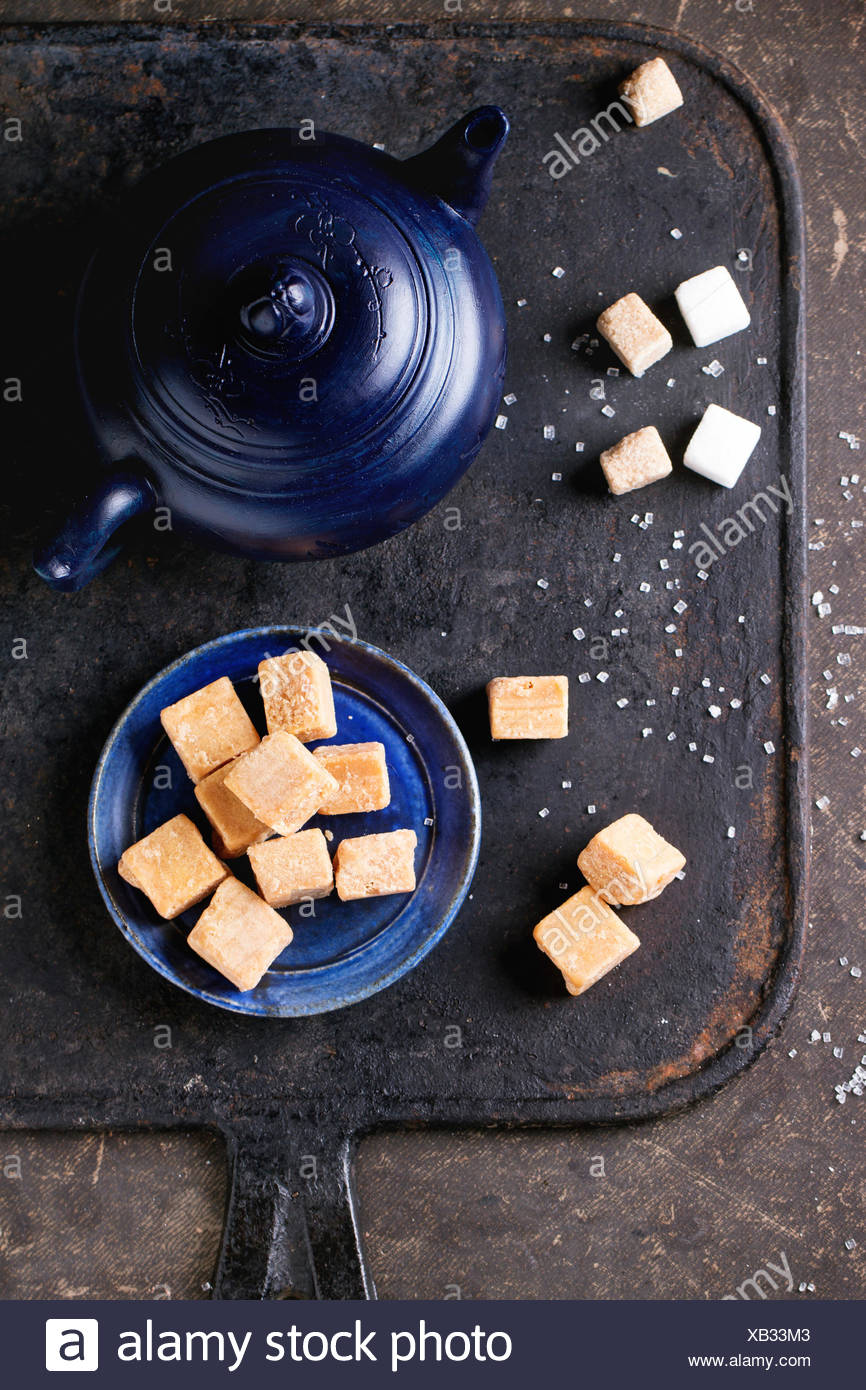 Blue ceramic plate with fudge candy ceramic teapot, served with sugar cubes over dark background. Top view - Stock Image