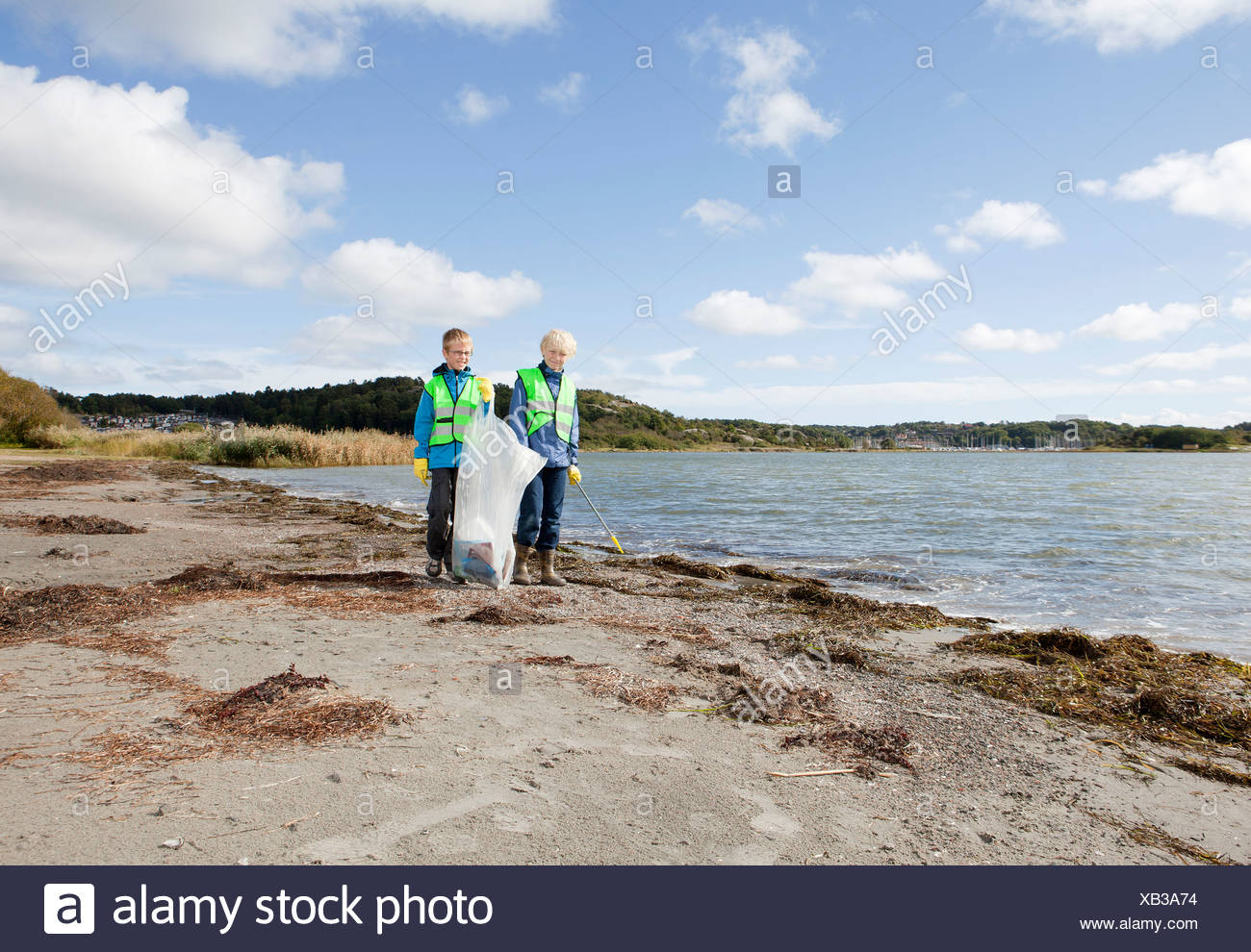 Boys in safety vests cleaning beach - Stock Image