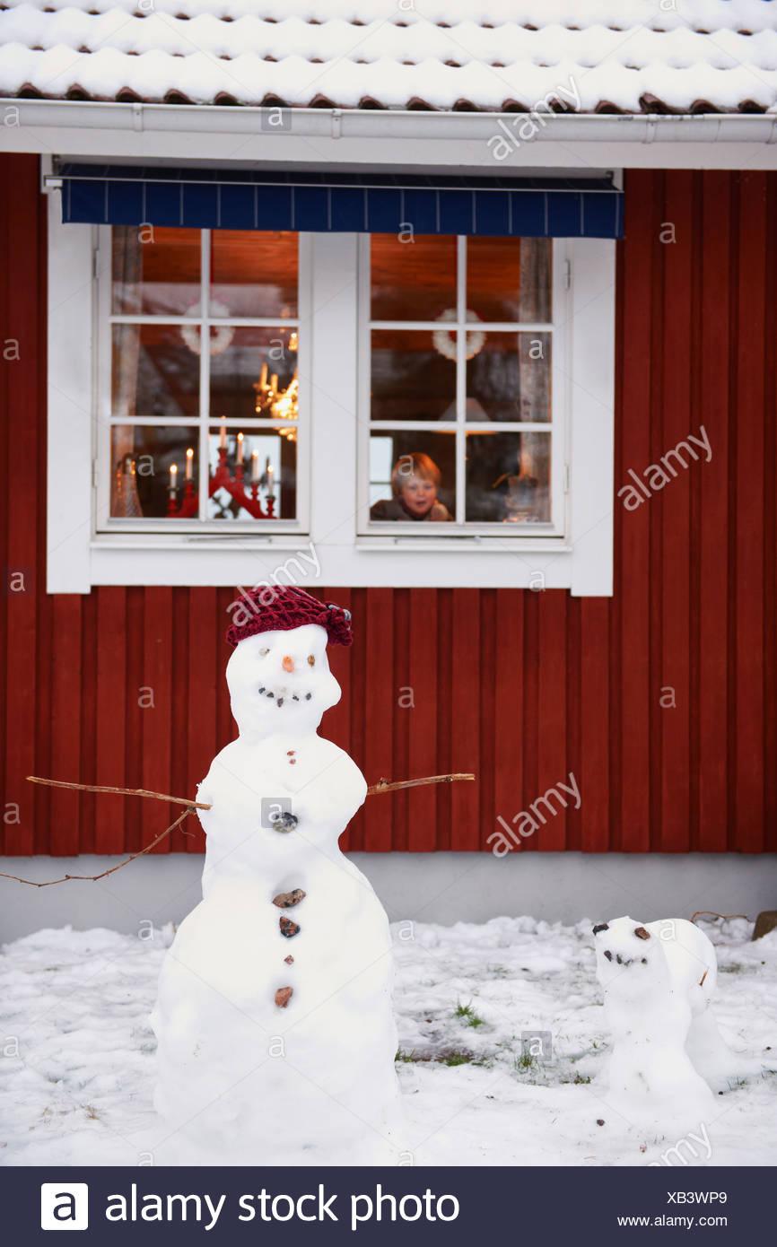 Snowmen standing outside house - Stock Image