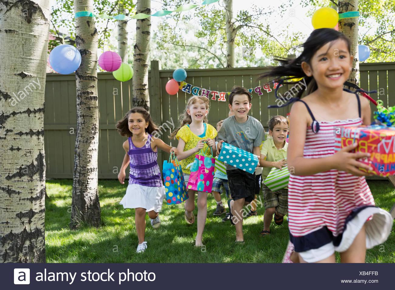 Backyard Gifts kids running with birthday gifts in backyard stock photo: 282227103