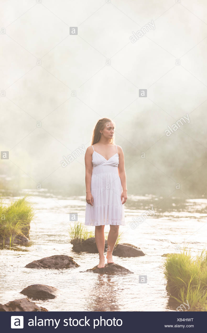 Woman wearing a white dress standing in river - Stock Image