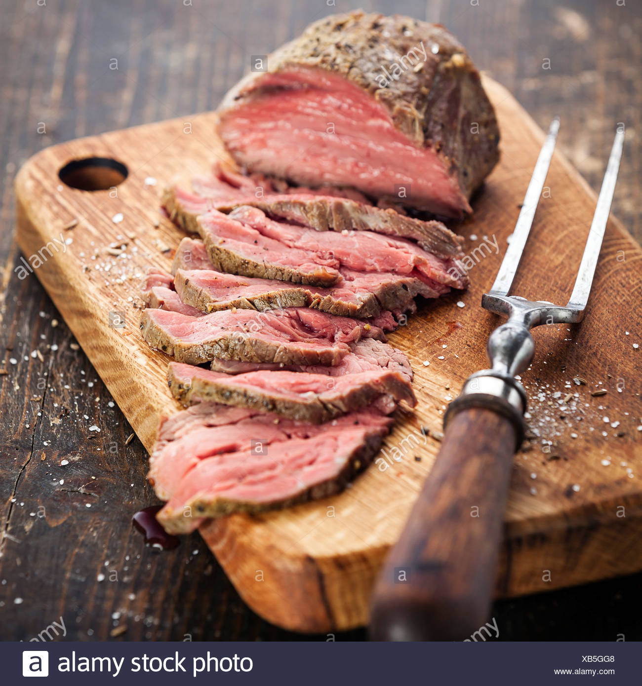 Roast beef on cutting board and meat fork - Stock Image