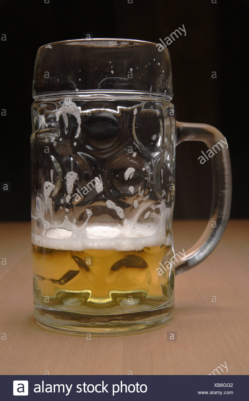 Half full beer mug on table, close up - Stock Image