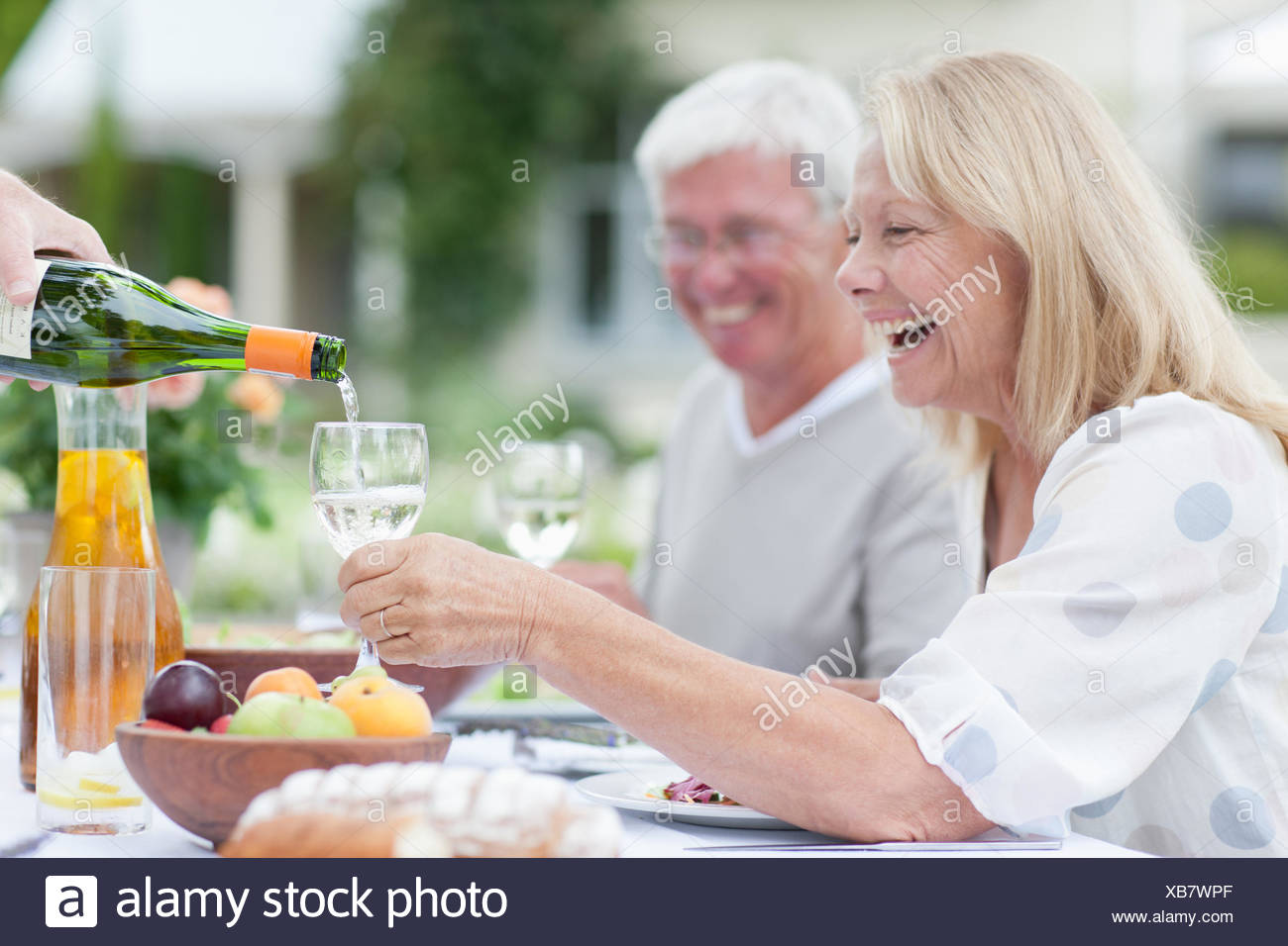 Senior adults enjoying wine at patio table - Stock Image