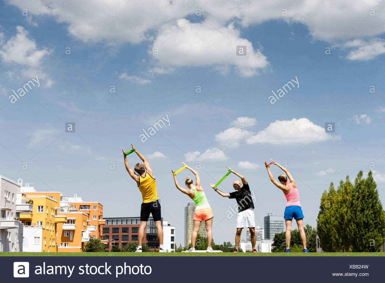 Four people exercising with rubber bands in park - Stock Image
