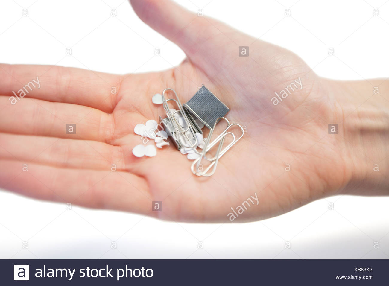 close-up of hand holding paper clips - Stock Image