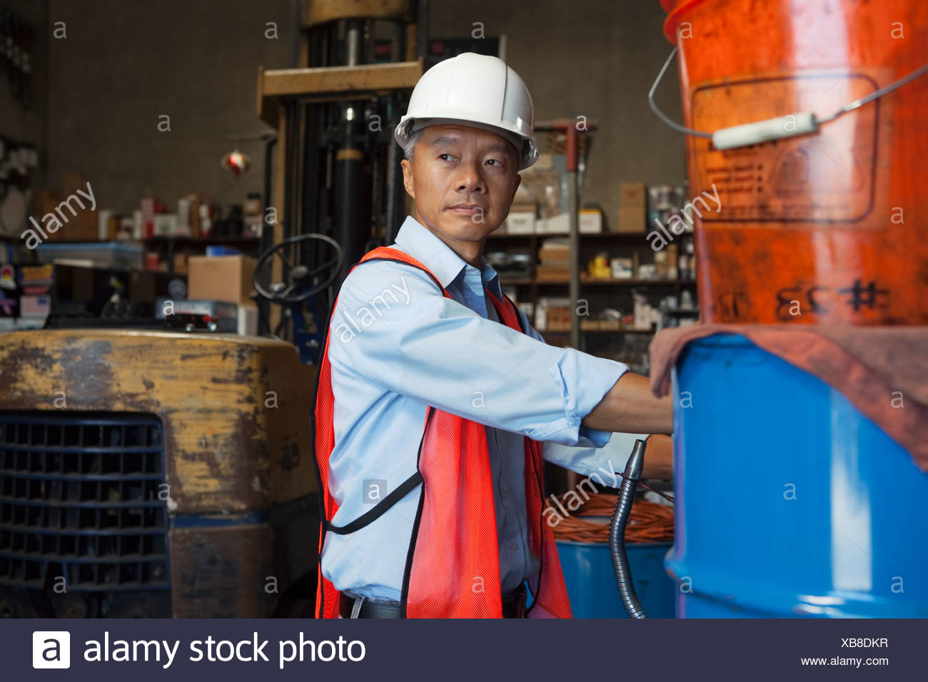 Middle-aged manager looking at something in warehouse - Stock Image