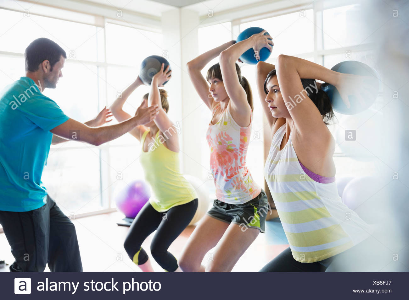 Women using medicine balls in fitness class - Stock Image