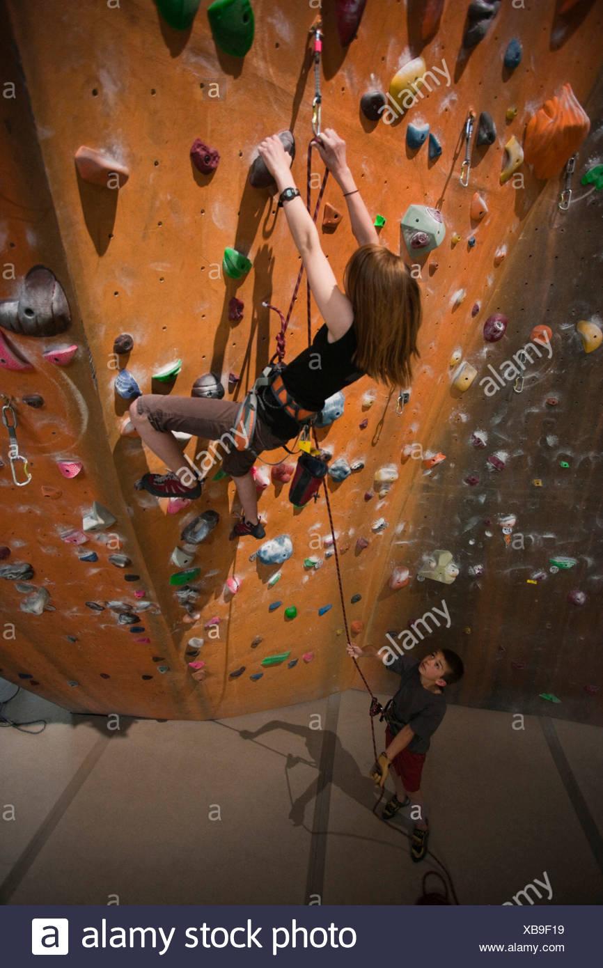 USA, Utah, Sandy, boy (12-13) assisting teenage girl (14-15) on indoor climbing wall - Stock Image