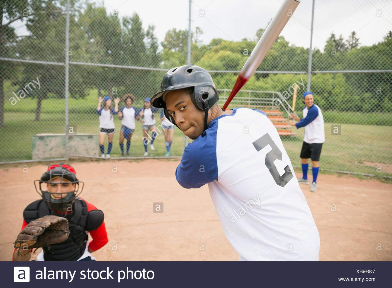 Baseball player ready for ball at home plate - Stock Image